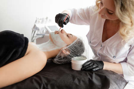 Beautician apply brush mask on clients face. enriches cells with oxygen. improves metabolism in the skin of the face.