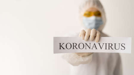 a woman in a special protective bone holds a sheet with the text coronavirus in her hands. The concept of the spread of the virus worldwide 2019-nCoV virus.