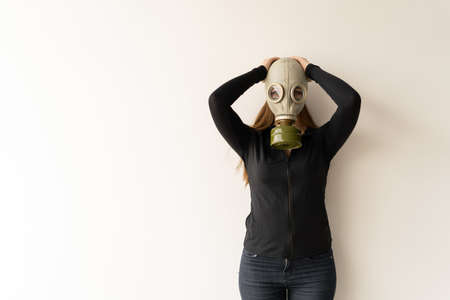 young woman protects herself from environmental pollution, gas mask on her face. White background, place for text.