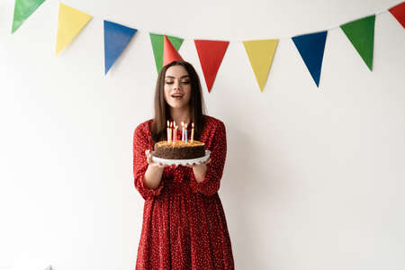 party in honor of the birth, a woman dressed in a red dress and a hat on her head is standing against a white wall, holding a delicious cake in her hands candles are burning on it. Make a jest, a place for text