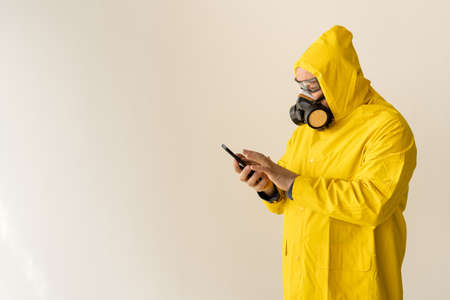 A man in a yellow chemical protection suit and a face mask clicks on the phone. Dialing a number. Quarantine isolation concept. Alone at home. place for text Stok Fotoğraf