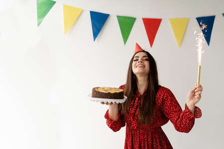 Beautiful and stylish girl in a red dress. Holiday birthday. Tasty cake and bengal fountain in the hands. Emotions of happiness and joy. Place for text