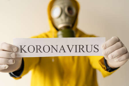 A man in yellow Hazmat suits and a gas mask holds an inscription with the text Coronavirus, gray background. Place for text