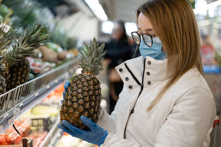 young woman wearing protective equipment buys citruses in a store. pineapples on the shelves of the supermarket. Concept of protecting the population during the COVID-19 pandemic.