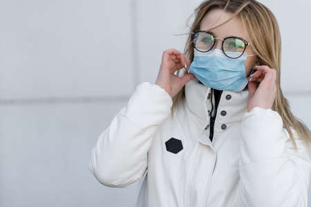 Beautiful young european woman in clothes outdoors with a medical mask on her face. Close up portrait of a woman in a respirator to protect against infection with influenza or coronavirus 版權商用圖片