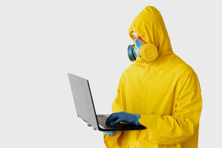 remote work during quarantine, a man dressed in a yellow protective suit holds a laptop in his hands and types in the text. Medical mask on the face. Coronavirus Warning, SARS-nCOV-2, COVID-19, 2019-nCOV. The concept of sitting at home during a pandemic. place for text Imagens
