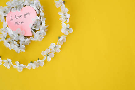 Flower tree cherry lie on a yellow background circle shape. A pink sheet of paper in the shape of a heart. The inscription i love you mom. Mother's Day and International Women's Day. Holiday in the spring. place for text