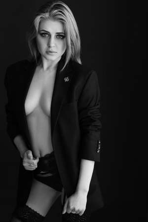 black and white photography. Young slender woman in a black jacket and without a bra. Sexy and passionate. Beautiful female figure.