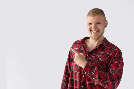 a young guy with blond hair dressed in a red man s shirt points a finger at a free place for text.