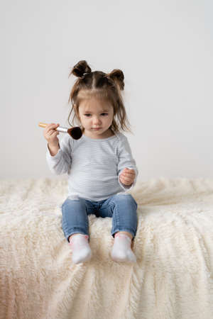 The little girl sits on the bed for two years and applies makeup. Powder brush. baby plays mom.