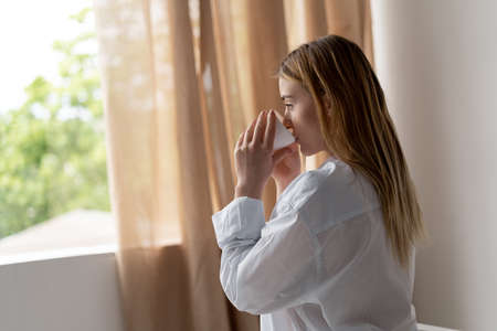 Happy young woman is drinking tea sitting in a chair at home. Beautiful morning. Blonde girl in a man s white shirt