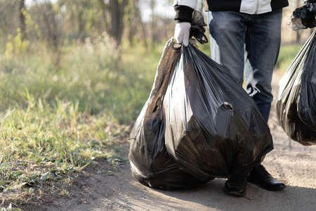A voluntary man holds two big black bags, a share of garbage collection in the park. Several complete packages