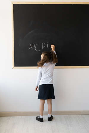 Clever girl in the school office. She stands in front of the board with her back to the camera. The schoolgirl has a uniform, and on her head hair is piled up in tails. Writes English letters. Studying of foreign language. Place for an inscription. Education concept.