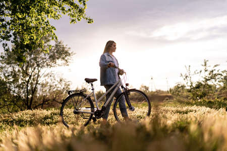 A young woman is walking near a bicycle in a city park at summer sunset. Blurred background with copy space area for text.