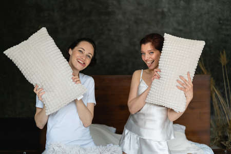 Two pretty girls on the bed in pajamas. They have white pillows in their hands. Weekend fun for girlfriends. Cohabitation of two women. Lesbian party.