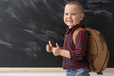 A happy schoolboy of 6-7 years old is standing at school near the blackboard with a school bag. He shows the class with two thumbs. September 1. Back to school. A schoolboy is wearing a shirt and jeans. Dark blackboard with chalk divorces. Place for text.