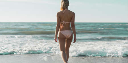 The girl is walking along the sandy beach. A slender woman is resting on the sea coast. The brunette in a swimsuit enters the ocean. The girl runs away from the wave.