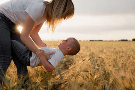 Young mother holding her baby in her arms in a wheat field. Children's laugh. Holidays with children in the countryside. Beautiful sunset. Family vacation concept. place for text