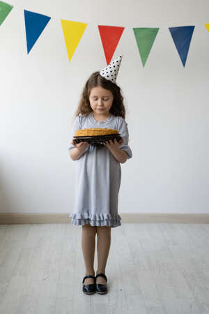 The girl has a birthday. She stands in the room and holds a cake in her hands. She has loose curly hair and a festive cap on her head. The walls in the room are light and decorated with multi-colored flags. Reklamní fotografie