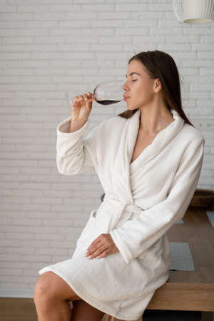 Beautiful n woman in white coat enjoying a glass of red dry wine sitting on the kitchen table in the hotel.