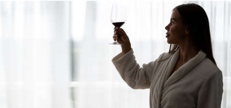 Young woman drinking a glass of red wine at home, smiling happy. Dressed in a white bathrobe.