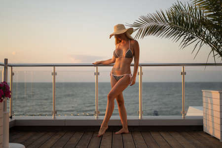 Young woman in a hat. The hat covers his eyes. Young blonde with graceful shapes. Holds the railing with one hand. Dressed in a gray separate swimsuit. Behind you can see the water surface and leaves of a decorative plant.