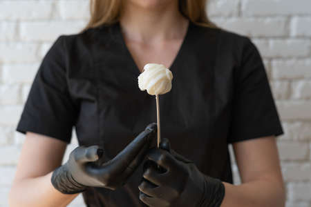 Sugar paste or wax on wooden spatula held by beautician in black latex gloves. Spa procedure, being beauty, cosmetology concept