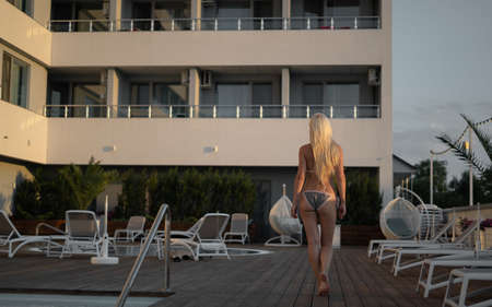 Sexy back of attractive beautiful woman in bikini walking by the pool on hotel background. Rear view. Sport, beauty, vacation concept. copy space, place for text