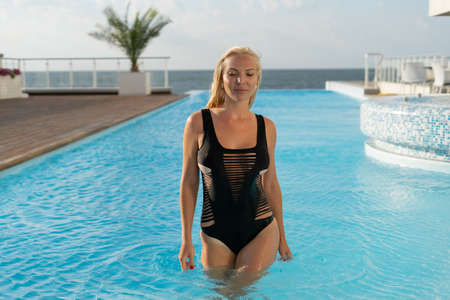 Girl in the pool at the hotel. Great resort location. Clear sky, sunny days. An unforgettable vacation. Horizon from the water surface. Clear water. Stok Fotoğraf