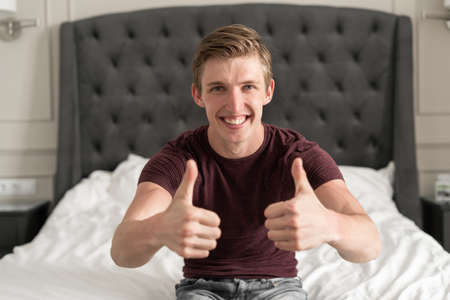 Portrait of a happy Caucasian young man talking on a video call. Sit at home on the bed. Cheerfully smile raise your thumb up. Great news