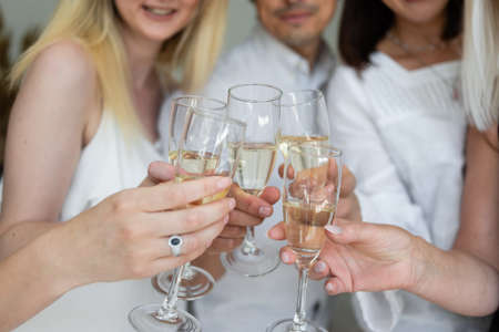 Close-up of friends hands holding glasses of champagne and making cheers. Corporate concept at work.
