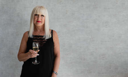 An adult woman on a gray background with a glass of champagne celebrates Christmas and New Year. Blonde aged Imagens