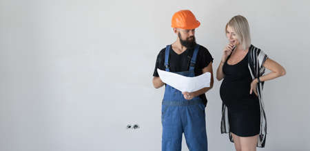 A man builder with a woman client is considering a repair plan. Pregnant girl. the concept of renovation in the apartment before the birth of the child. Place for text