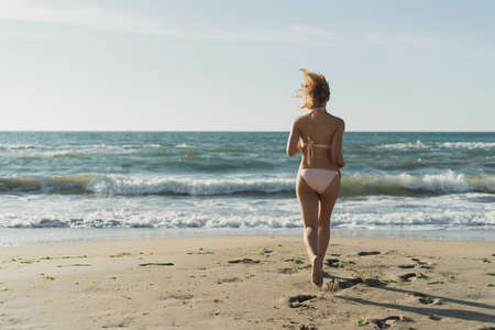 Young beautiful woman runs to the ocean. Swimsuit is dressed on a sports body. Sea waves. The concept of relaxing on the beach. Place for text Imagens