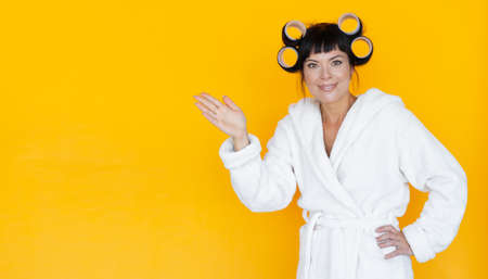 young beautiful woman housewife in a white robe. curlers on the head. Yellow background. emotion of surprise on the face, with a hand pointing to an empty seat.