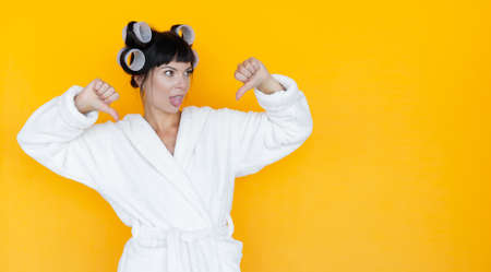 young beautiful woman housewife in a white robe. curlers on the head. Yellow background. looks at an empty space. She took out her tongue and put her thumbs down