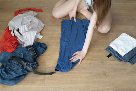 top view of female hands fold clothes. The process of sorting things. House cleaning concept.