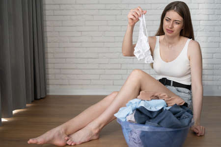 beautiful caucasian woman sits on the floor and sorts dirty clothes. holds white female underpants in her hands. House cleaning concept. Place for text.