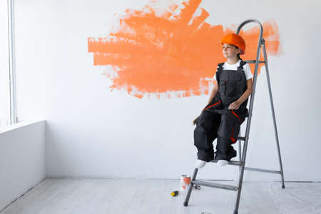 little girl builder dressed in clothes of a builder and an orange hard hat on her head. sitting on the stairs looking away at the stain. Home renovation concept. Place for your text.