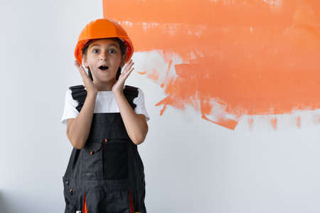 Portrait of a charming girl in an orange hard hat on her head. raised her hands to her face with an emotion of surprise. Copy space Standard-Bild