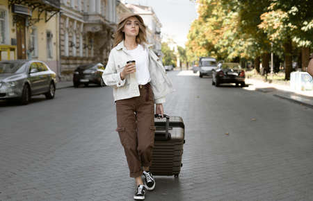 tourist woman with a suitcase down the street in a European city, tourism in Europe. walks down the street pulling luggage with him. coffee in a disposable paper cup. copy space.
