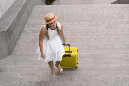 Beautiful tourist girl travels. Pulls a heavy, large yellow suitcase up the steps.