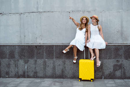 Beautiful two female tourist twins are sitting near a large yellow suitcase and smiling. Pointing with a finger to an empty space for text. Stock fotó