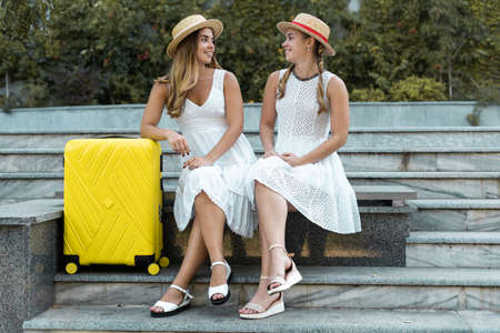 two female twin tourists are sitting near a yellow suitcase on the steps. flight waiting concept Stock fotó