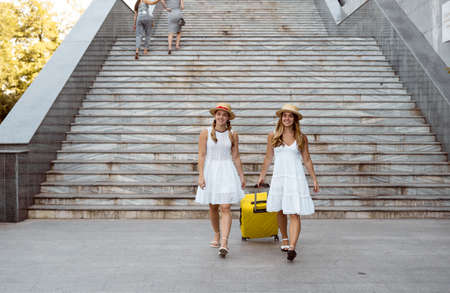 two female twin hikers are walking near the stairs. pull a large yellow suitcase. Copy space.