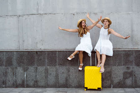 two female twin tourists are sitting near a yellow suitcase with their arms outstretched to simulate flight. Flying an airplane concept Stock fotó