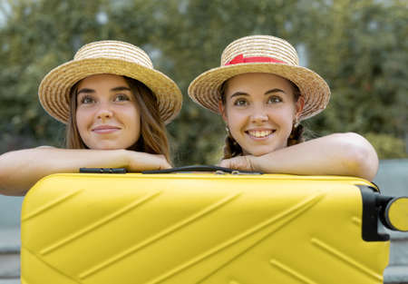 two female twin tourists are sitting near a yellow suitcase. Close-up portrait