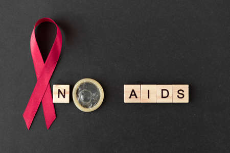 Red ribbon. Concept for World AIDS Day. black background, copy space. no AIDS. Baner