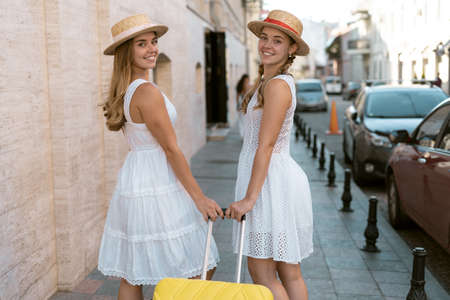 The sisters of the traveler visit a new city while traveling in Europe and they are happy. Walking down the street with a smile and a suitcase in hand.