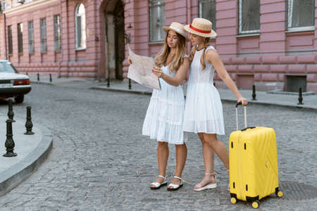 Two girls sisters travel and love tourism. They look at the map in their hands and look for their way to the hotel. One sister is holding a yellow suitcase with things.